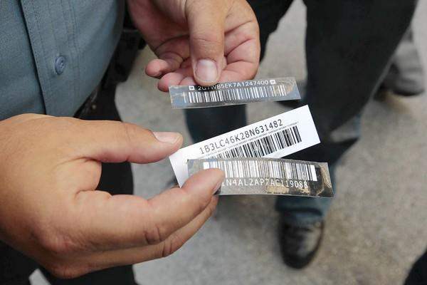 Elmer Garza, an Illinois secretary of state police investigator, demonstrates Monday how counterfeit labels for vehicle identification numbers were used to steal a 2008 Escalade. State law enforcement agencies on Monday announced the arrests of 21 people in connection with a Northeast Illinois car theft ring.