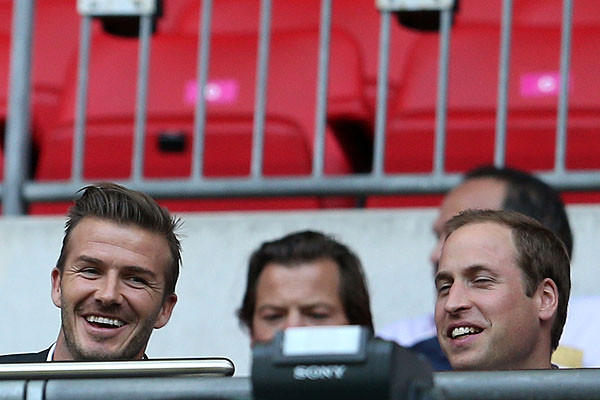 David Beckham, left, and Prince William watch a first round of men's soccer group A match between Great Britain and United Arab Emirates.