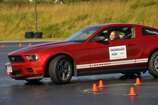 "Hayden Hutzell, 17, of Ellicott City, learns the mechanics of how to control a skid by driving in a car equipped with special oversized castor wheels between the rear tires that safely simulates a skid at slow speeds. The Ford ""Driving Skills for Life"" instructors explain a technique for handling skids called CPR: correct, pause and recover."
