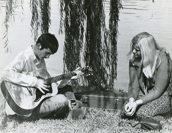 Jerry Benefield, then 17, plays guitar as Barbra Podkowicz, also 17, listens along the shore of Lake Eola in 1967.