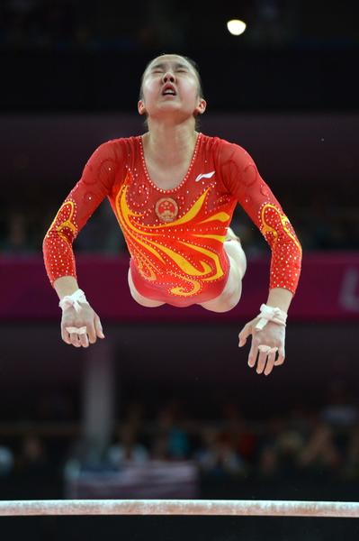 Chinese gymnast Huang Qiushuang competes on the uneven bars during the Women's team final of the Artistic Gymnastics event on July 31.