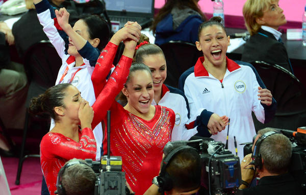 USA gymnasts Alexandra Raisman (left) and Jordyn Weiber (center),  McKayla Maroney and Kyla Ross (right) celebrate winning the goal medal in the women's gymnastics team competition during the London 2012 Olympic Games at North Greenwich Arena.