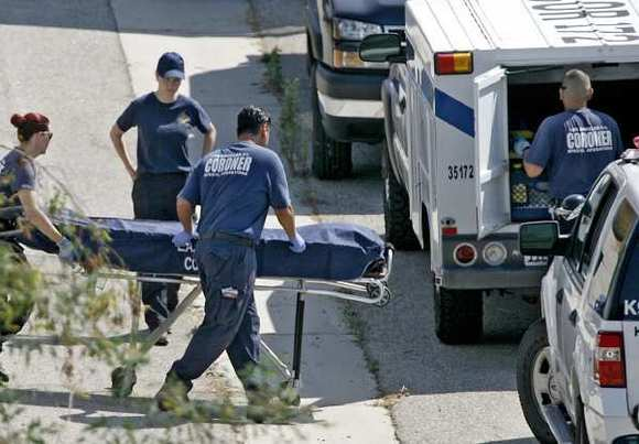 The body of a person found on a trail behind St. Francis Xavier Church in Burbank is loaded onto a L.A. County coroner's truck on Tuesday, July 31, 2012.