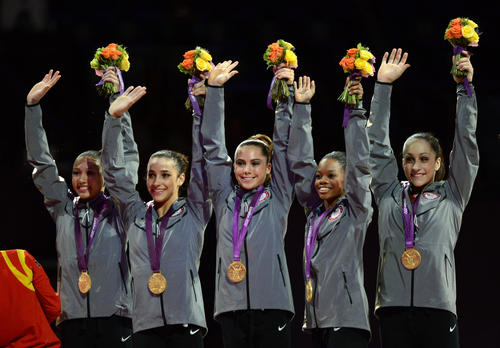 Gold medalist Team US Kyla Ross, Alexandra Raisman, Mckayla Maroney, Gabrielle Douglas and Jordyn Wieber celebrate on the podium of the women's team competition of the artistic gymnastics event of the London Olympic Games on July 31, 2012 at the 02 North Greenwich Arena in London.