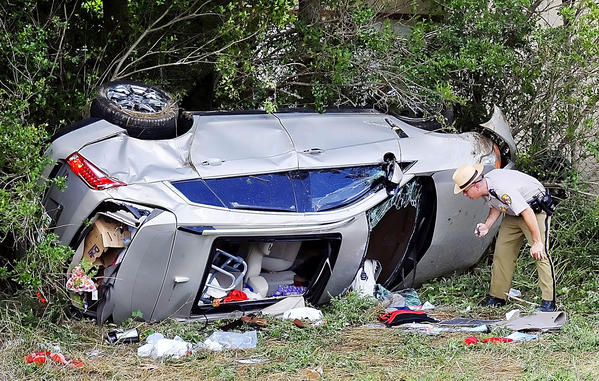 A Maryland State Police trooper looks inside a vehicle that rolled down an embankment Tuesday after a fatal two-vehicle accident in the southbound lane of Interstate 81 south of the Maryland-Pennsylvania state line.