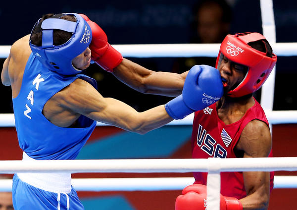 Jamel Herring of the United States, right, takes a blow from Daniyar Yeleussinov of Kazakhstan in  men's light-welterweight  boxing. Yeleussinov went on to win the fight.