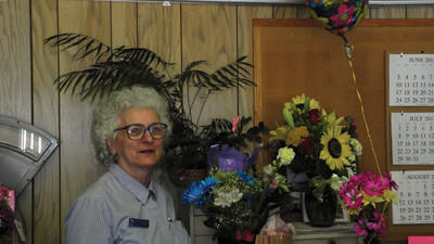 Nancy Gindlesperger, 34-year Davidsville postmaster, stands smiling among a few of the many flowers and balloons she received from co-workers and community members before retiring on Tuesday.
