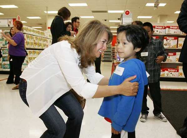 Hilda Morovati, of Toluca Lake, introduces herself to Christian Vargas, 5, at Target in Glendale where about 30 local children matched up with volunteers holding $80 gift cards to shop for school supplies and clothing.