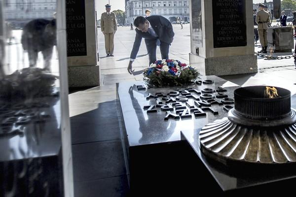 Republican presidential candidate Mitt Romney lays a wreath at the Tomb of the Unknown Soldier in Warsaw, Poland, where campaign aide Rick Gorka gave reporters an impromptu tongue-lashing.