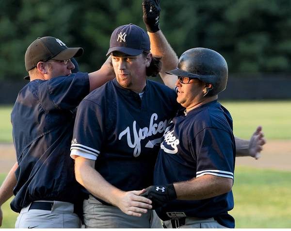 Northern Yankees designated hitter Darrin Lenhart (far right) is congratulated by pitcher Jake Argue (center), after Lenhart scored the winning RBI in the 7th inning after win against the Limeport Bulls at the conclusion of Tri-County League baseball playoff game at the Scherersville baseball fields on Tuesday.