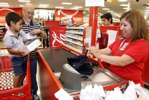 Keanu Fernandez, 4, left, purchased a variety of clothes and shoes with the help of Burbank Noon Kiwanis member Philip Jue, center, during the annual Salvation Army's Burbank Corps Back-to-School Target Shopping Spree at the Burbank Target.