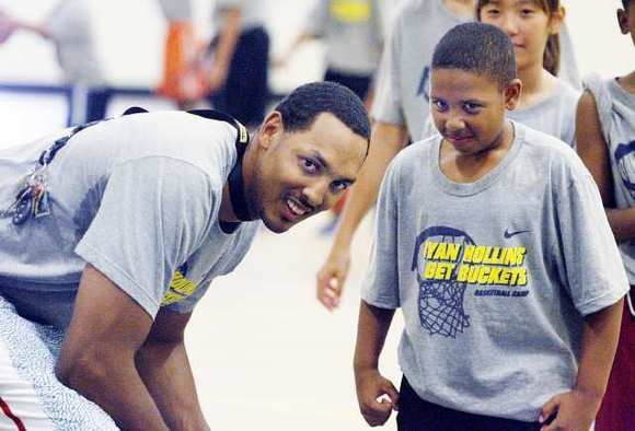 Ryan Hollins, of the Los Angeles Clippers and a Muir High graduate, smiles as one of the kids during drills at John Muir High for the Ryan Hollins Basketball Skills Camp for youth players from age 8 to 18 in Pasadena.