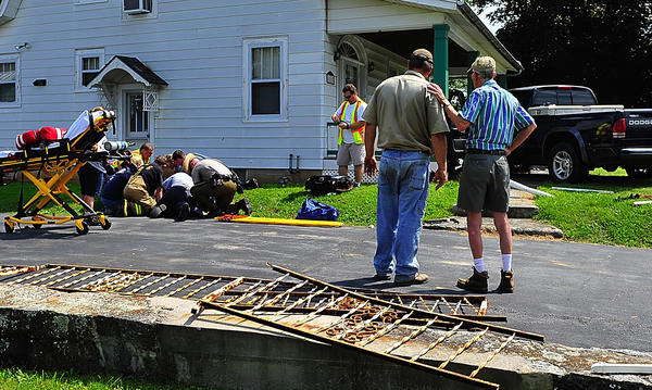 Neighbors talk Tuesday after a truck struck a house at 8117 Sharpsburg Pike, while rescue workers perform first aid on the driver. The driver, who was not identified, was taken to Meritus Medical Center with minor injuries, a Washington County Emergency Services dispatcher said. The incident was reported at 2:47 p.m. A person inside the home at the time of the crash called police, the dispatcher said.