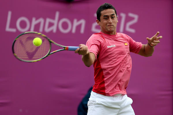 Nicolas Almagro of Spain returns a shot to Steve Darcis of Belgium during the third round of Men's Singles Tennis on Day 5 of the London 2012 Olympic Games at Wimbledon on August 1 in London.