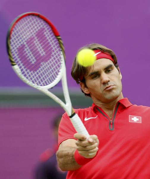 Switzerland's Roger Federer returns to Uzbekistan's Denis Istomin in their men's singles tennis match at the All England Lawn Tennis Club during the London 2012 Olympic Games on August 1.