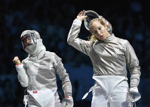 U.S. fencer Mariel Zagunis, right, reacts after conceding a hit against South Korea's Kim Ji Yeon during their Women's sabre semifinal bout as part of the fencing event of London 2012 Olympic games.