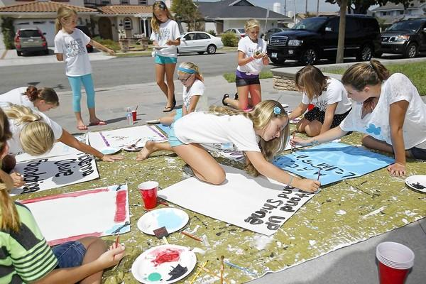 Sophie Roberts, 10, center, one of McKenna Claire Wetzel's best friends, makes a sign with other close friends and family for the lemonade stands they will set up Sunday. Last year, McKenna, 7, died from a brain tumor. Her family and friends hope to raise awareness for brain cancer research with process from the stands.