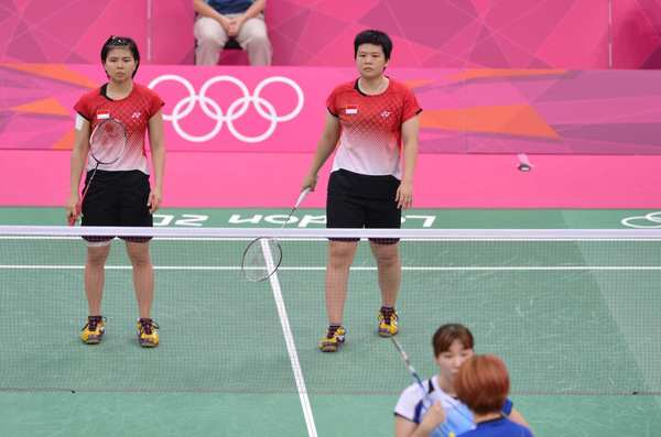 Indonesia's Greysia Polii, left, and  Meilana Jauhari watch as South Korea's Ha Jung-eun talks with Kim Min-jung after referees stopped  match. Olympic officials disqualified both pairs.