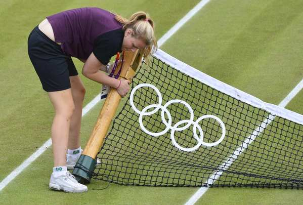 A member of the ground staff fixes the tennis net before the third-round men's singles match between Belgium's Steve Darcis and Spain's Nicolas Almagro at Wimbledon. Almagro won the watch.