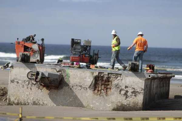 Workers in Newport, Ore., use a cable-cutting system to divide into sections a Japanese dock that made its way to Oregon's coast after last year's tsunami.