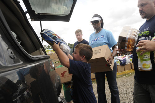 Nick Blanchette, 7, of Thompson, left,  places food in the back of a car at the Comcast Theater in Hartford as part of a second annual food distribution program which benefited a reported 800 families from the area Wednesday.
