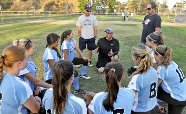 Crescenta Valley-Footill Junior All-Star softball team coaches, from left, Drummond Schaffer, Will Thayer and Tyson Howard talk with the team before it headed to Arizona for the Western Regional Tournament, which starts Thursday.