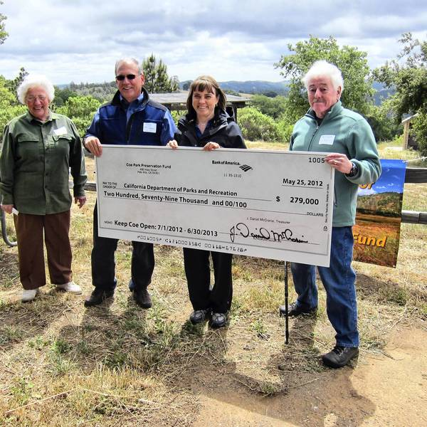 A symbolic check for $279,000 to help keep Coe Park open is held by, from left to right, Ann Briggs, president of Coe Park Preservation Fund; Dan McCranie, treasurer of Coe Park Preservation Fund; Ruth Coleman, then-state parks director, and Robert Patrie, founder and board member of Coe Park Preservation Fund.