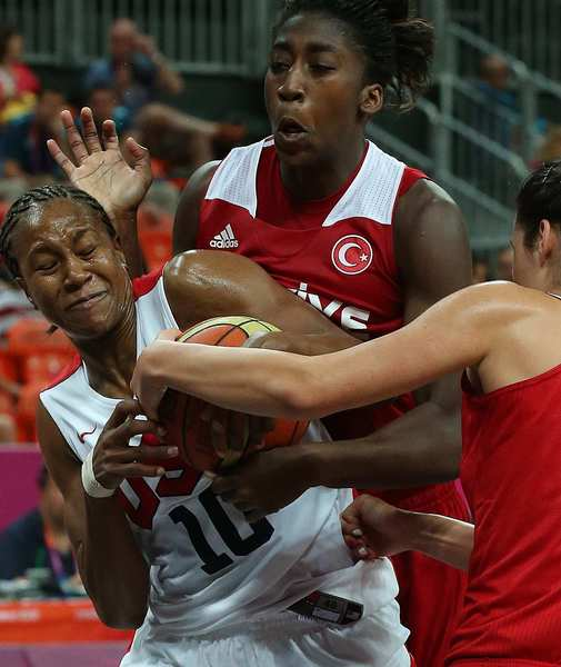 Team USA's Tamika Catchings, left, wrestles the ball from Turkey's Kuanitra Hollingsvorth in the second half of a preliminary game at the London 2012 Olympics.