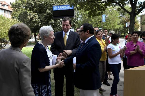 Juan Rangel, CEO of UNO Charter Schools, shakes hands with Sister Patricia Crowley, Prioress of St. Scholastica, on Tuesday after announcing that the St. Scholastica Academy will be leased by UNO for a charter school. Between them is Ald. Joe Moore, 49th.