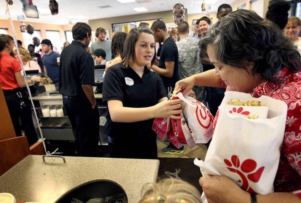 "Chick-fil-A cashier Alana Crowther hands Joy Edwards her order Wednesday evening at the Mercury Blvd. location in Hampton during what many are calling ""Chick-fil-A Appreciation Day."""