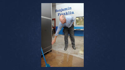 John Barth of Benjamin Franklin Plumbing, Somerset, gestures toward the high water mark in the business on Wednesday.