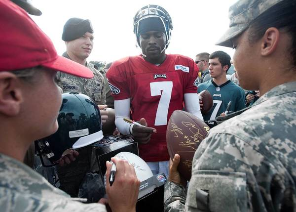 Philadelphia Eagles quarterback Michael Vick (7) signs autographs for members of the military on Wednesday during training camp at Lehigh University.