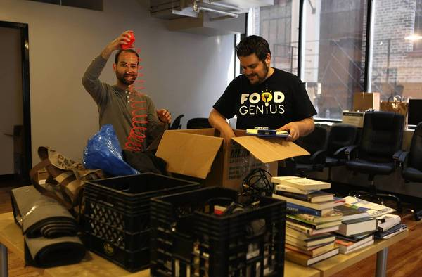 Food Genius co-founders Eli Rosenberg, left, and Justin Massa begin to organize their new office space on West Erie Street in River North on Wednesday minutes after movers left.