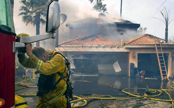 A Riverside County firefighter rests his head in the extreme heat while trying to save a house fully engulfed in flames during the Volcano brush fire near Murrieta.