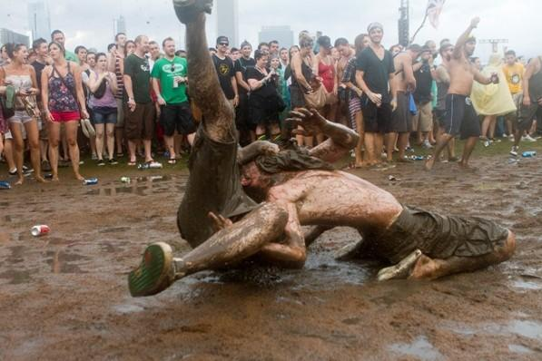 Fans dance and wrestle in the mud while The Arctic Monkeys perform at Lollapalooza Sunday, August 7, 2011 in Chicago, IL.
