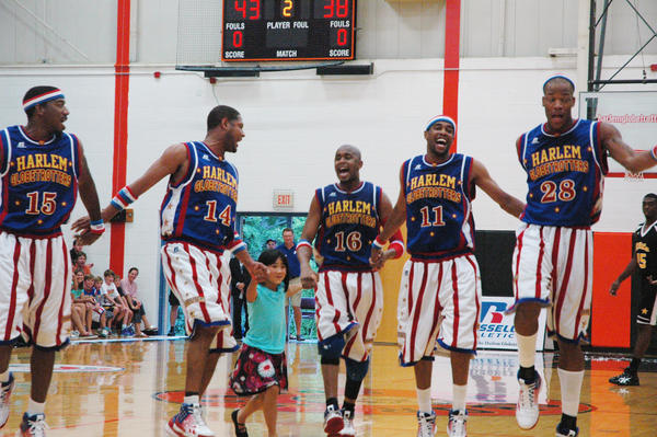 Members of the Harlem Globetrotters skip around the court at Harbor Springs High School with Addy Hawley, 7, during the team's appearance at the school on Wednesday night.