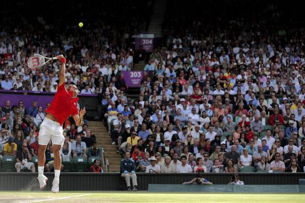 Roger Federer of Switzerland serves the ball to John Isner of the United States during the Quarterfinal of Men's Singles Tennis on Day 6 of the London 2012 Olympic Games at Wimbledon.