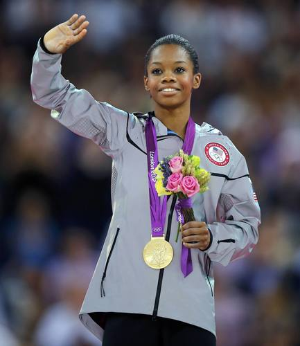 Gabrielle Douglas of the U.S. waves on the podium after receiving her gold medal during the women's individual all-around gymnastics final in the North Greenwich Arena during the London 2012 Olympic Games August 2, 2012.