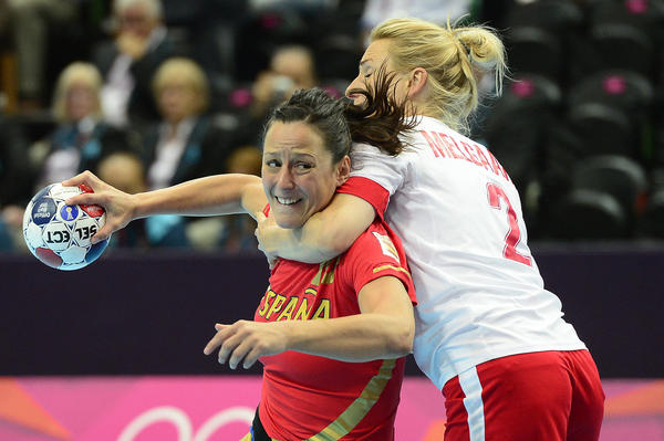 Denmark's pivot Mette Sall  puts stranglehold on Spain's rightback Marta Mangue Gonzalez  during the women's handball preliminaries.