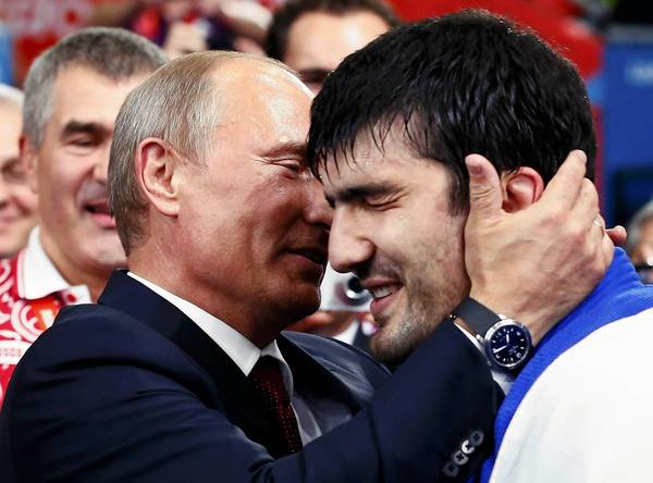 Russian President Vladimir Putin congratulates Russia's Tagir Khaibulaev after he defeated Mongolia's Tuvshinbayar Naidan in their men's -100kg final judo match at the London 2012 Olympic Games.