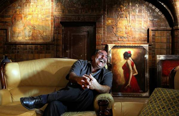 Exuberant businessman Charles Aslan sits amid murals by Ernest Batchelder at what began as a chocolate shop in 1914 in downtown Los Angeles.