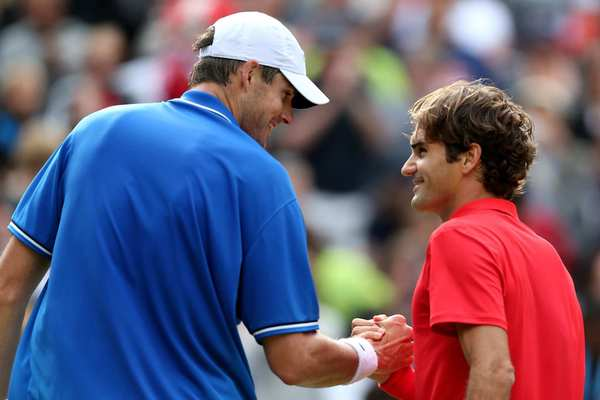 Roger Federer, right,  shakes hands with John Isner after defeating him in the men's singles quarterfinal.