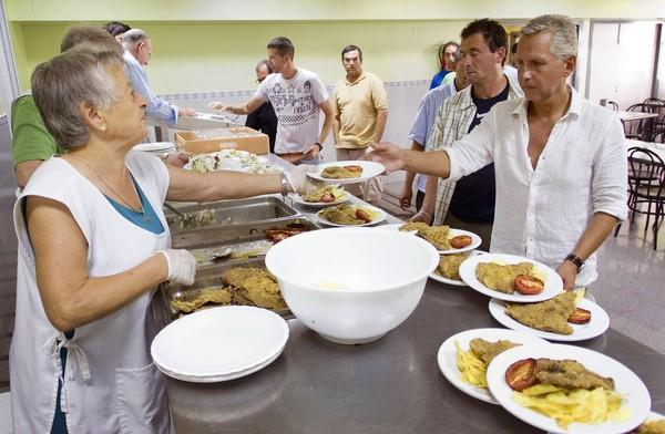Volunteers serve meals at a charity dining hall in Valencia, Spain. Close family ties are another factor that has enabled the nation to withstand a nearly 25% unemployment rate.