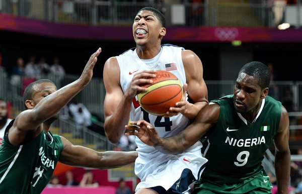 Team USA's Anthony Davis, center, drives to the basket, but is fouled by Nigeria's Chamberlain Oguchi, right, as Richard Oruche helps on defense in the second half.