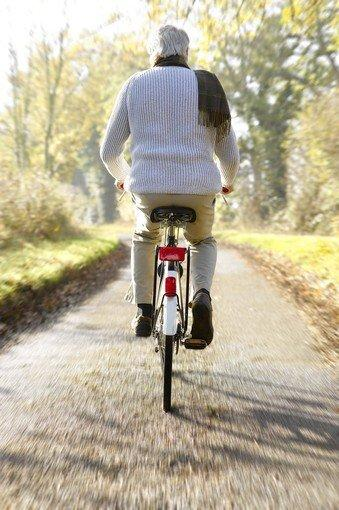 Senior man riding bicycle on countryside lane. (Dougal Waters/ Photographer's Choice)