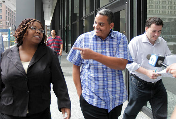 Eugene Mullins, center, a one-time former aid to Cook County Board Chairman Todd Stroger, leaves the Dirksen U.S. Federal Courthouse with his lawyer, Brunell Donald-Kyei, left.