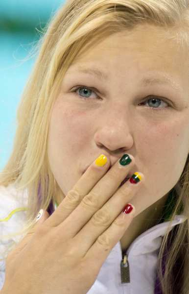 Ruta Meilutyte of Lithuania, with her national flag's colors painted on her nails, blows a kiss to the crowd at the aquatics center after winning the women's 100-meter breaststroke.