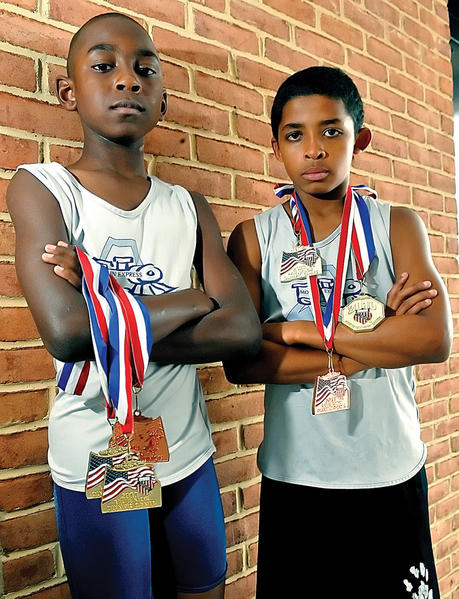 Jalyx Hunt, left, and James Searcy -- shown with their national medals last year in this Herald-Mail file photo -- were back at it again Wednesday at the AAU Junior Olympic Games in Houston. Searcy won a national title in the high jump for the third straight year, while Hunt placed second in the event.