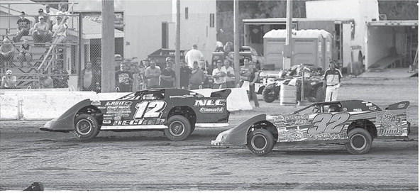 Chad Becker (12) and Pat Weisgram (32), both of Aberdeen, make their way down the backstretch at Brown County Speedway this summer. Racers spend countless hours and dollars before they hit the local track every Friday night. Racing takes place at the local oval at 7:30 tonight. American News Photo by John Davis