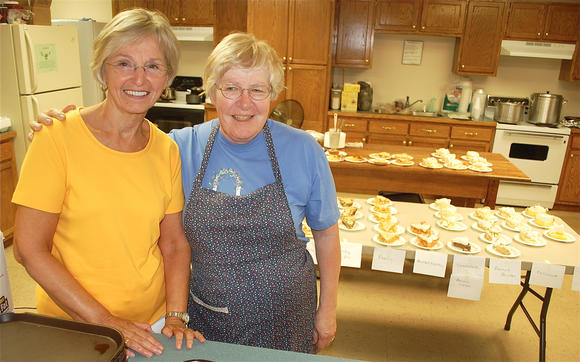Nancy Wilcher, left, and Connie Coppings of Westside Community United Methodist Church near Hustonville serve up about 40 pies a day to yardsale shoppers, with proceeds going to the church¿s good works.